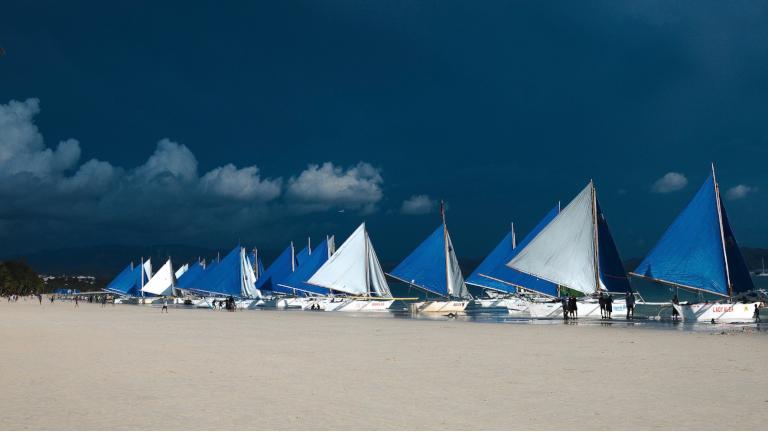 gamle traditionelle både på filippinerne. her trukket ind på stranden så glade forbipasserende kunne få en sejltur