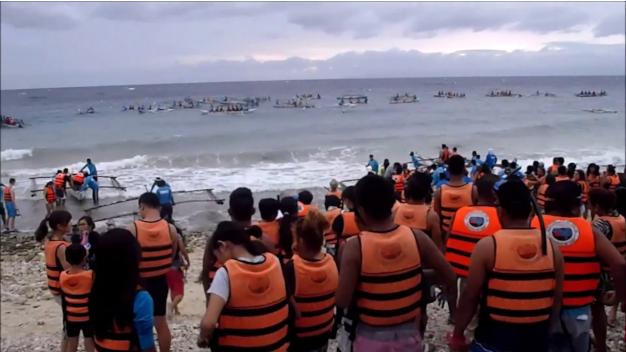 folk står i kø på stranden for at komme på en af 30 både som hele tiden sejler rundt ovenpå hvalhajerne