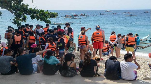 massere af turister står klar på stranden. de mange turister stresser hvalhajen